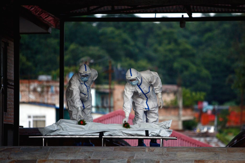 Nepalese army personnel wearing protective suit pay tribute to the body of a COVID-19 patient at a crematorium in Kathmandu, Nepal, Aug. 12, 2020. The Nepali ...