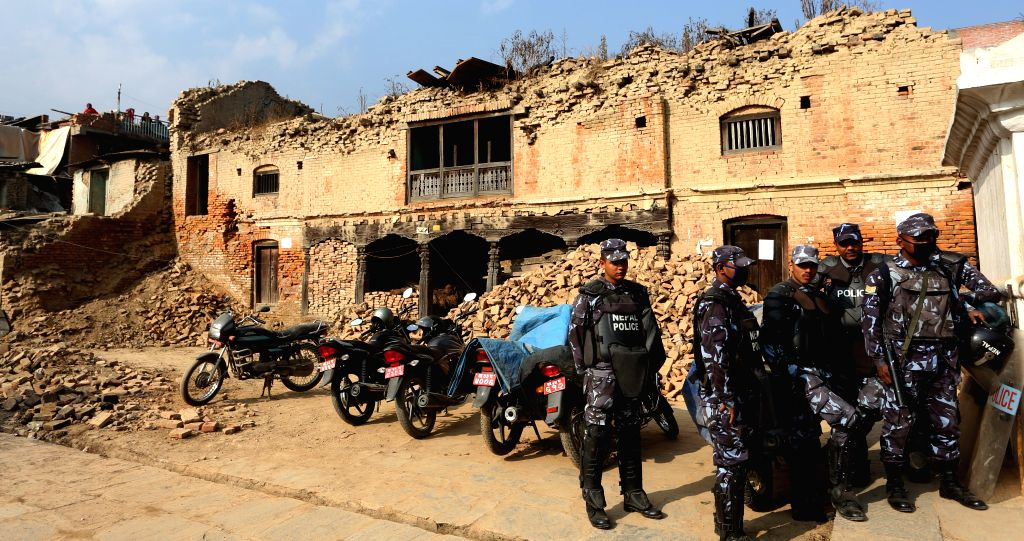 Nepalese policemen stand guard in front of damaged buildings during a national reconstruction mega-campaign at Bungamati in Lalitpur, Nepal, Jan. 16, 2016. Nepal ...
