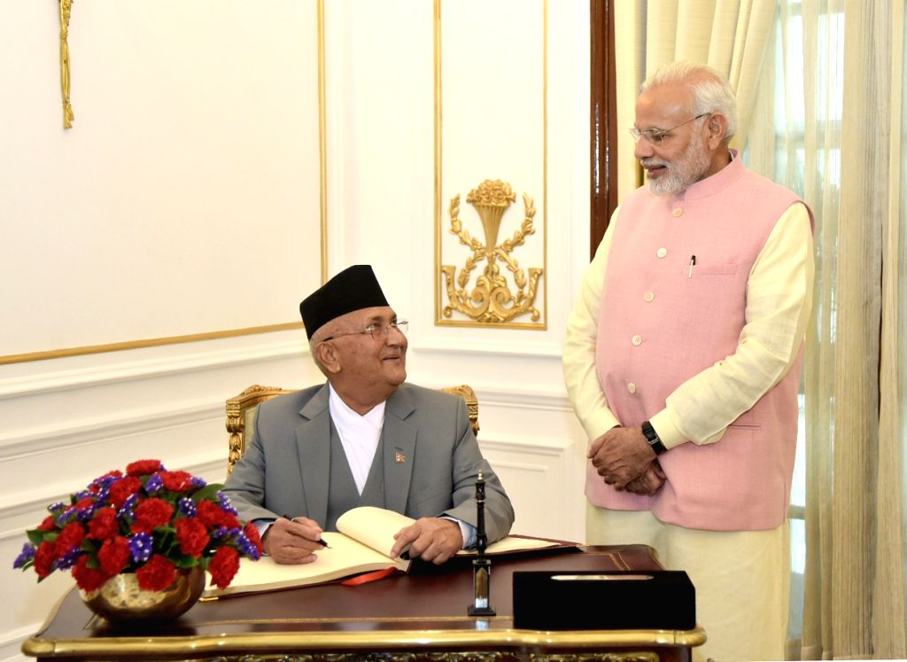 Nepalese Prime Minister K.P. Sharma Oli signs the visitors' book of Hyderabad House, in New Delhi on April 7, 2018. Also seen Prime Minister Narendra Modi. - K., Narendra Modi and P. Sharma Oli