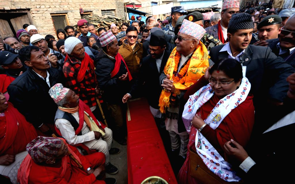 Nepalese Prime Minister KP Sharma Oli (R) talks with villagers as he arrive to participate in the official launch of a national reconstruction mega-campaign at ... - K