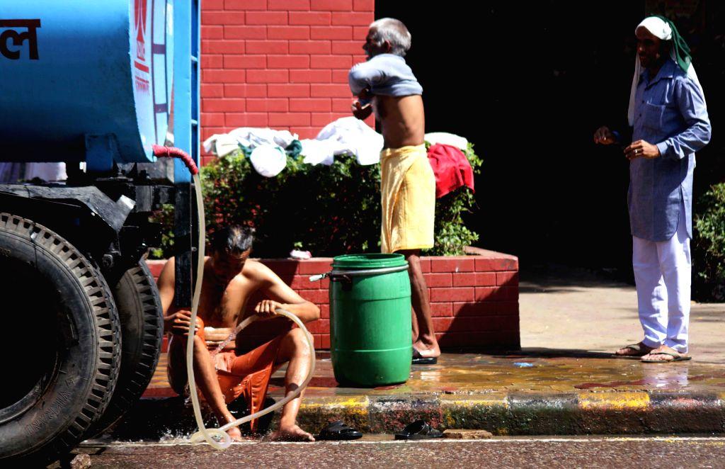A man bathes on footpaths of Delhi as days get warmer day-by-day.