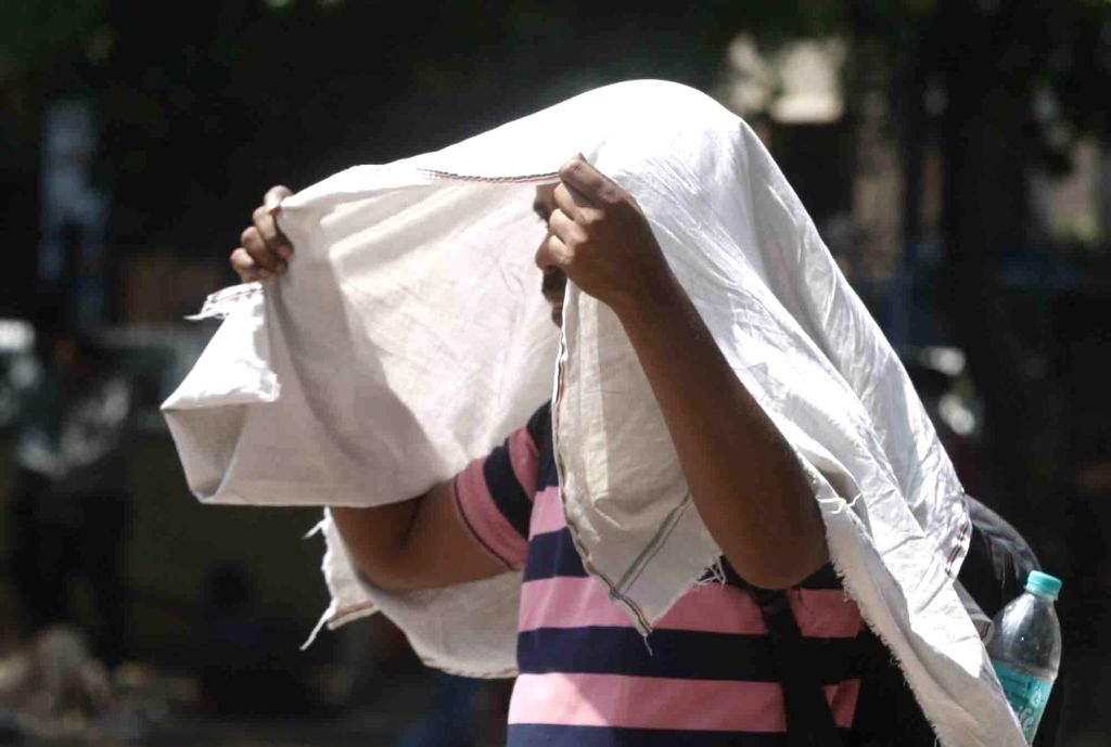 :New Delhi: A man covers his head to protect himself from the scorching heat on a hot sunny day, in New Delhi on May 22, 2018. (Photo: IANS).