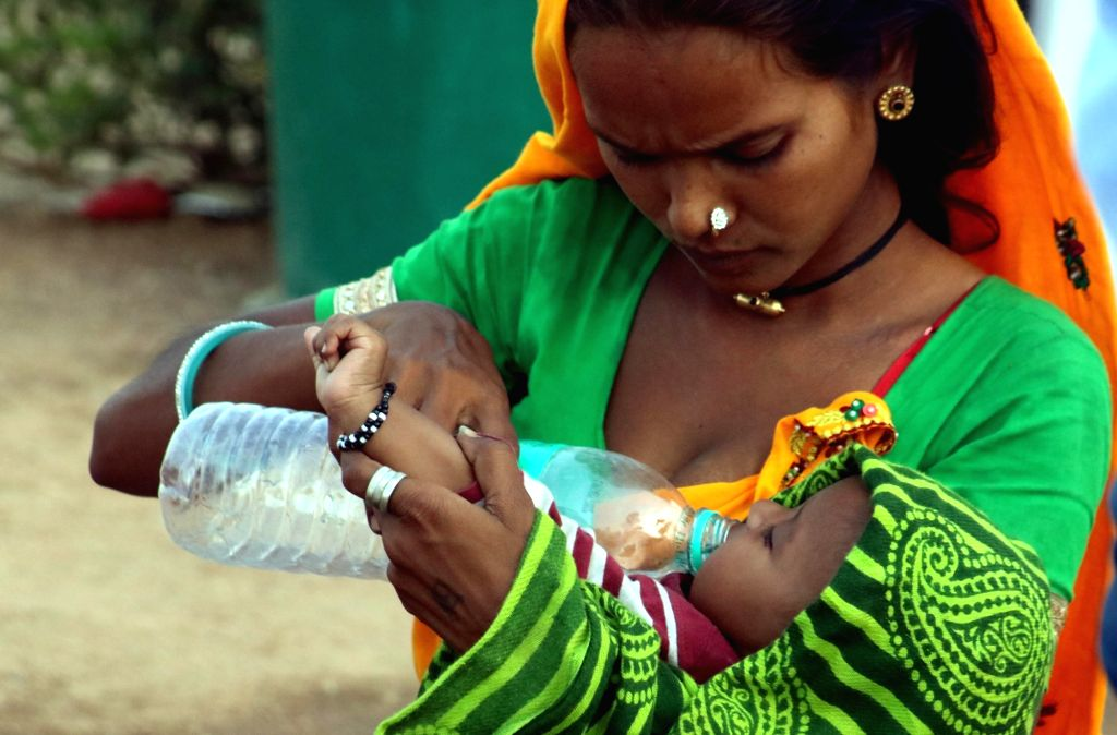 New Delhi: A mother feeds water to her child on a hot day in New Delhi, on May 17, 2016. (Photo: IANS)