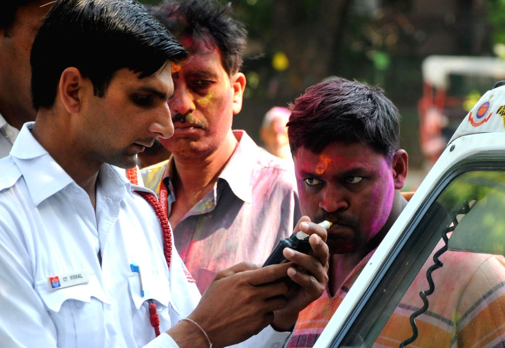 A traffic policeman carries out breathalyzer test on a driver in New Delhi, on March 6, 2015.