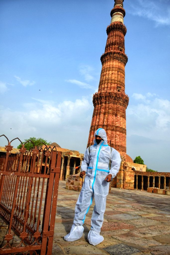 New Delhi :  A worker wearing PPE suits and sanitizing Qutub Minar monument area after Archaeological Survey of India (ASI) allow to reopne all monuments in Delhi on Tuesday 15 June 2021.