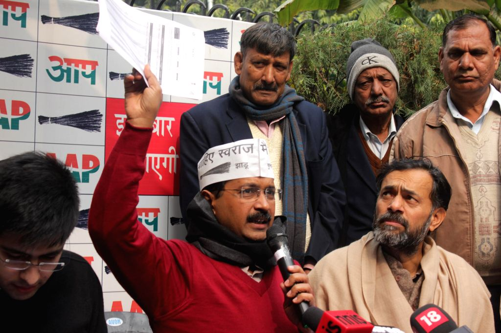 Aam Aadmi Party (AAP) leader Arvind Kejriwal addresses a press conference at North Avenue in New Delhi, on Jan 14, 2015. Also seen party leader Yogendra Yadav. - Arvind Kejriwal and Yogendra Yadav