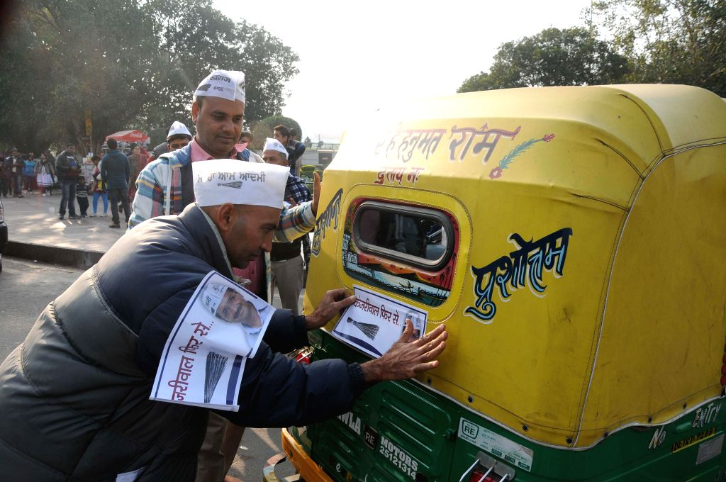 Aam Aadmi Party (AAP) volunteers paste pamphlets on auto rickshaws during an election campaign ahead of Delhi Assembly elections expected to be held in February 2015, in New Delhi.