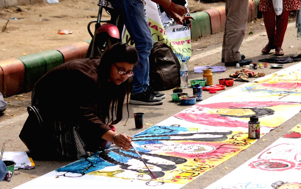 An artist paints a picture during a programme organised to observe International Women's Day at Jantar Mantar in New Delhi, on March 8, 2015.