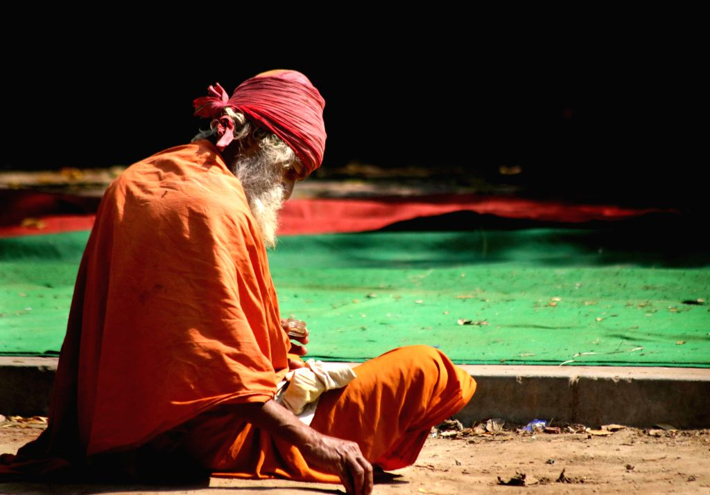 An ascetic sits on a pavement near Jantar Mantar in New Delhi, on March 7, 2015.