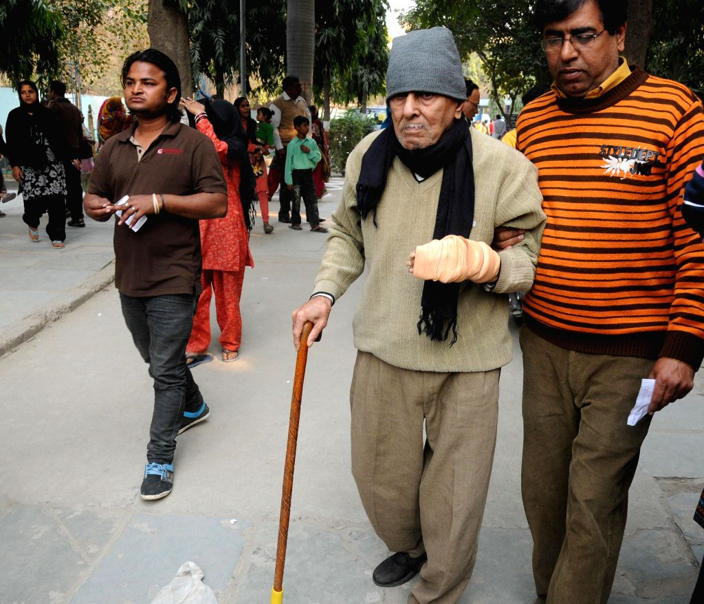An elderly gentleman arrives to cast his vote at a polling booth during Delhi Assembly Polls in New Delhi, on Feb 7, 2015.
