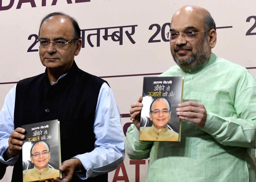 "New Delhi: BJP chief Amit Shah and Union Finance Minister Arun Jaitley launch Jaitley's book ""Andhere Se Ujale Ki Aur"" in New Delhi on Oct 20, 2016. - Arun Jaitley and Amit Shah"