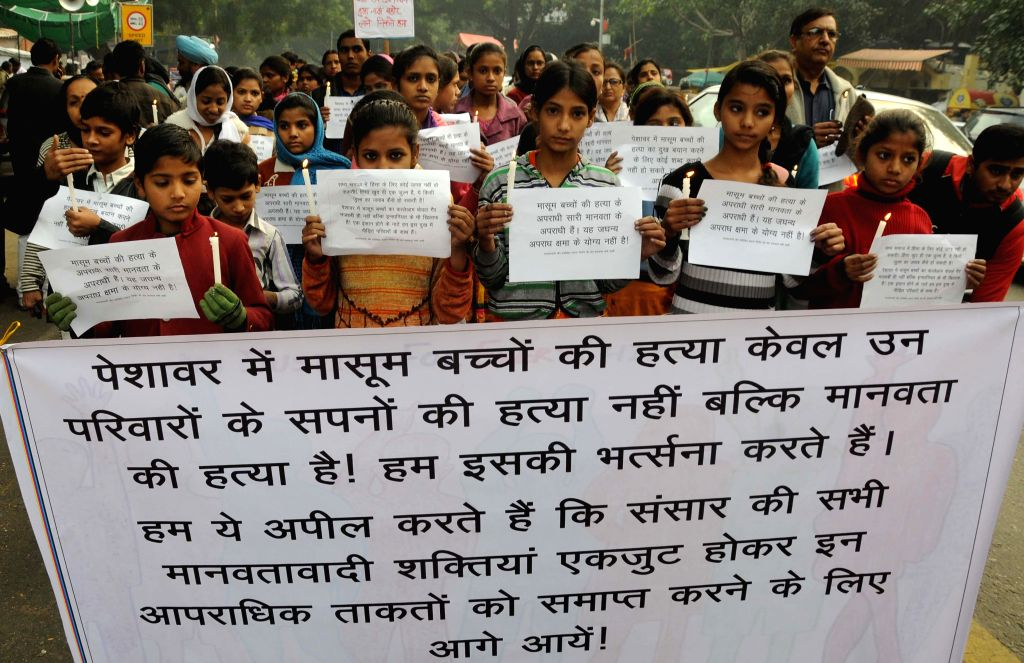Children condemn the Tuesday's attack on the Army Public School in Peshawar, Pakistan, that claimed 148 lives mostly those of children, in New Delhi on Dec 18, 2014.