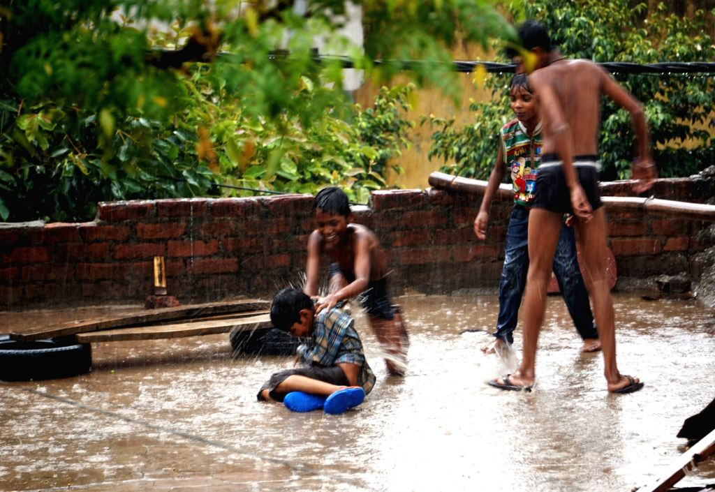 New Delhi: Children enjoy themselves during rains at a rooftop, in New Delhi on July 4, 2019. (Photo: IANS)