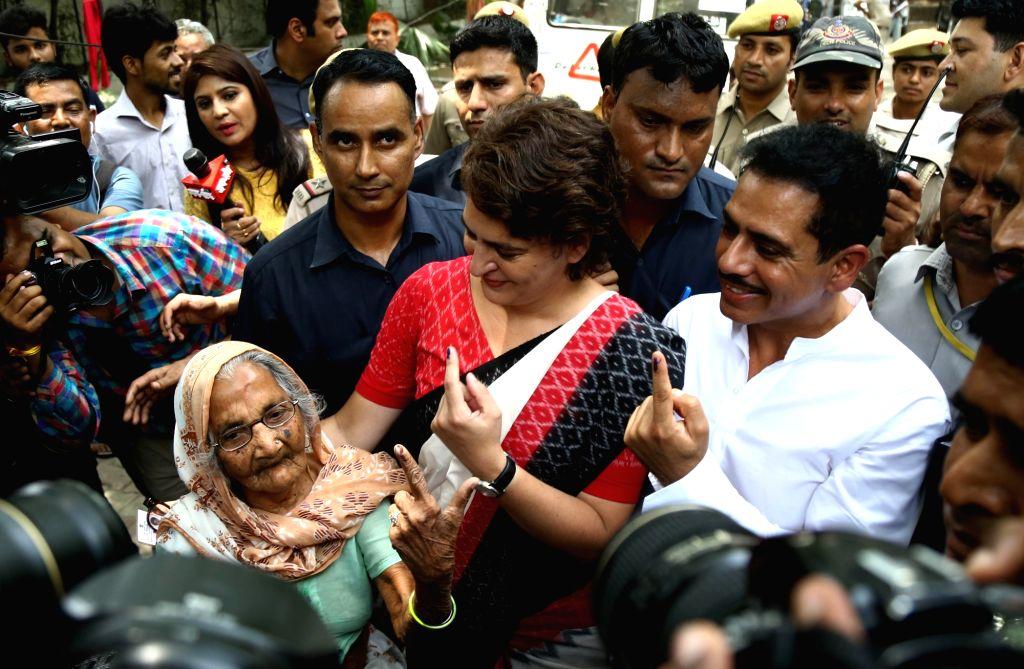 New Delhi: Congress leader Priyanka Gandhi Vadra interacts with an elderly lady at Sardar Patel Vidyalaya where she arrived to cast vote in New Delhi's Lodhi Estate on May 12, 2019. Also seen her husband Robert Vadra. (Photo: IANS) - Priyanka Gandhi Vadra and Sardar Patel Vidyalaya