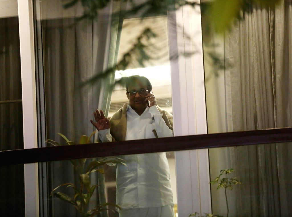 New Delhi: Former fiance Minister P. Chidambaram peeping through window at his residence after returning home from Tihar Jain on bail, in new Delhi on Dec 4, 2019. (Photo: IANS) - P. Chidambaram and Tihar Jain