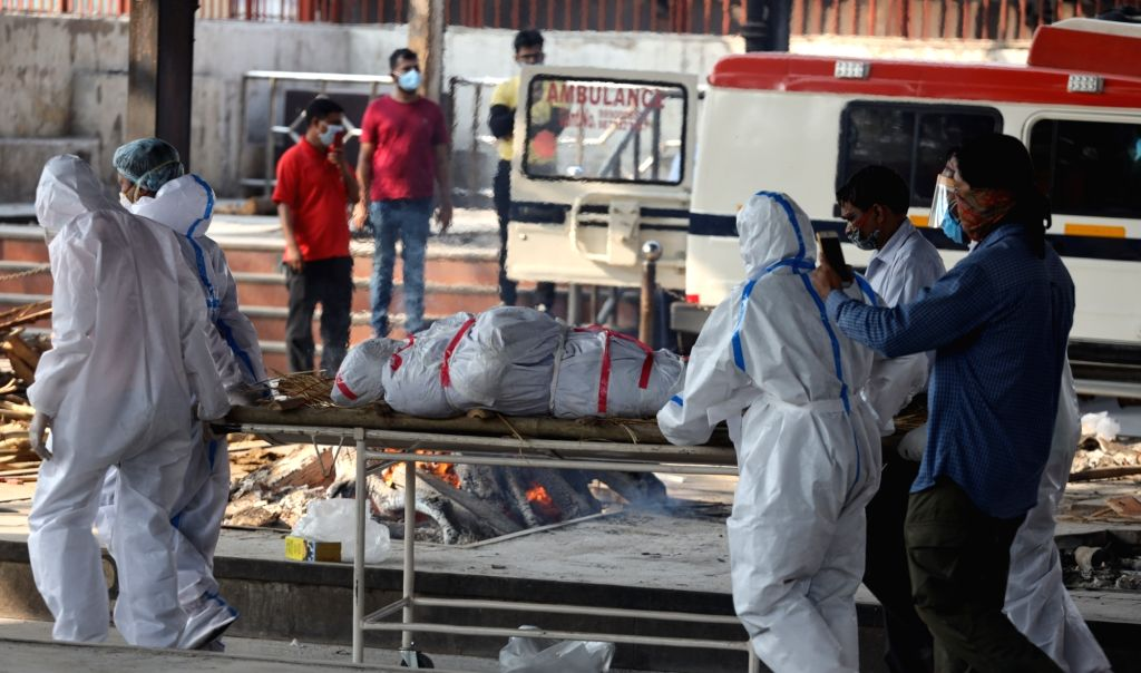 New Delhi: Health workers wearing Personal Protective Equipment (PPE) suits bring the body of a patient who succumbed to COVID-19 at Nigambodh Ghat in New Delhi on June 12, 2020. (Photo: IANS)