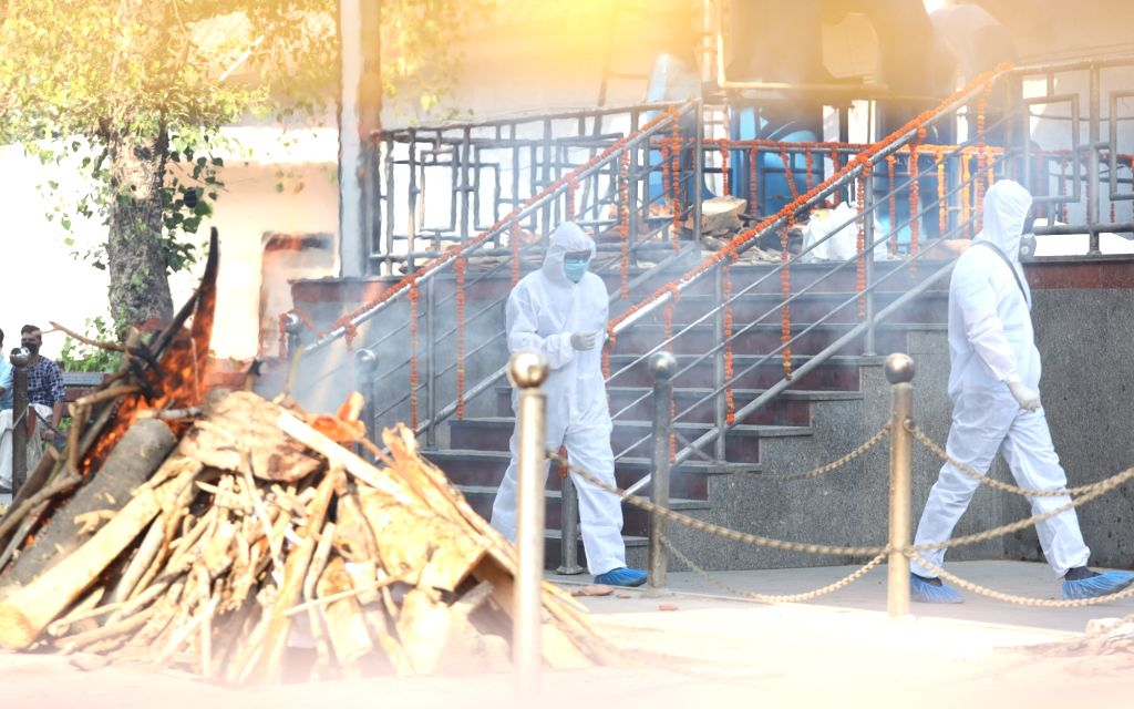 New Delhi: Health workers wearing Personal Protective Equipment (PPE) suits cremate the body of a patient who succumbed to COVID-19 at Nigambodh Ghat in New Delhi on June 12, 2020. (Photo: IANS)