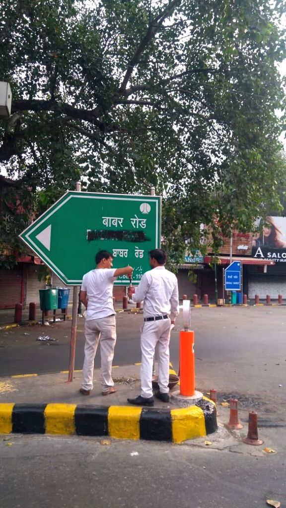 """New Delhi: Hindu Sena activists blacken the signage for Babar Road at Bengali market demanding that it be renamed after a """"great Indian personality""""., in New Delhi on Sep 14, 2019. (Photo: IANS)"""
