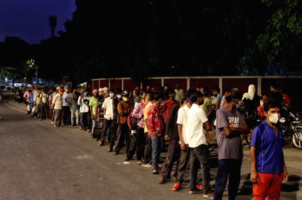 New Delhi : Homeless stand in a que for food during the food distribute on going third week lockdown due to Covid-19 pendamic at Sacred Heart Cathedral Church, Gol dak khana in New Delhi on Friday ...