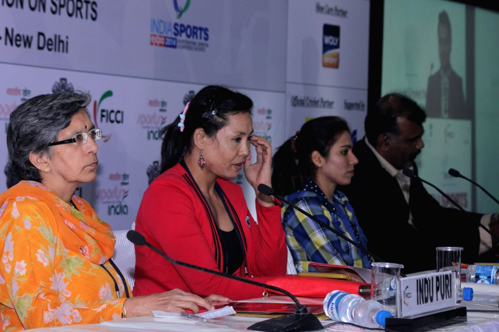 Indian boxer Laishram Sarita Devi, who won bronze medal in 2014 Asian Games, with track and field athlete Priyanka Pawar, who won gold in the 2014 Asian Games and others during a programme