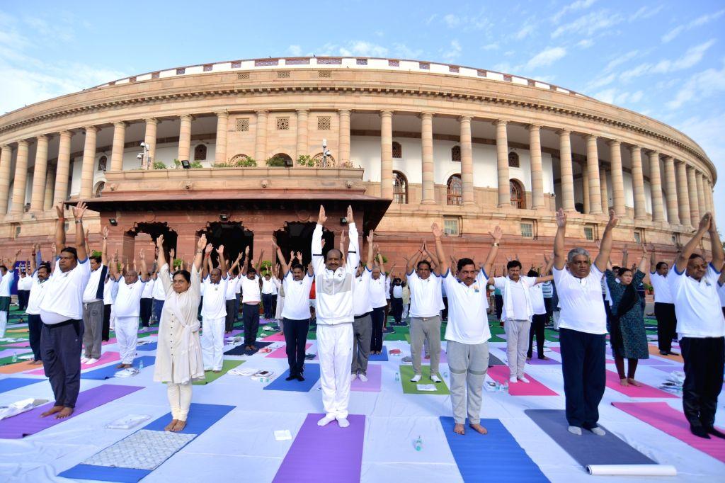 New Delhi: Members of Parliament practice yoga asanas -postures- on International Yoga Day 2019 at Parliament premises in New Delhi on June 21, 2019. (Photo: IANS)