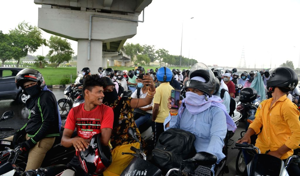 New Delhi: Motorcyclists take shelter under a flyover during sudden  rains, in New Delhi on June 26, 2020.