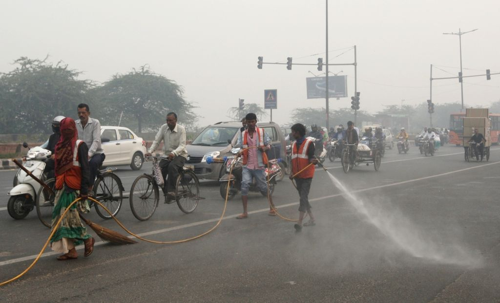 New Delhi Municipal Corporation (NDMC) workers sprinkle water on a street as a measure to curb pollution in New Delhi, on Nov 5, 2018.