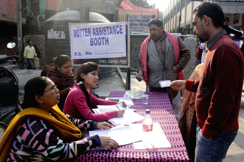 People arrive to cast their votes at a polling booth during Delhi Assembly Polls in New Delhi, on Feb 7, 2015.