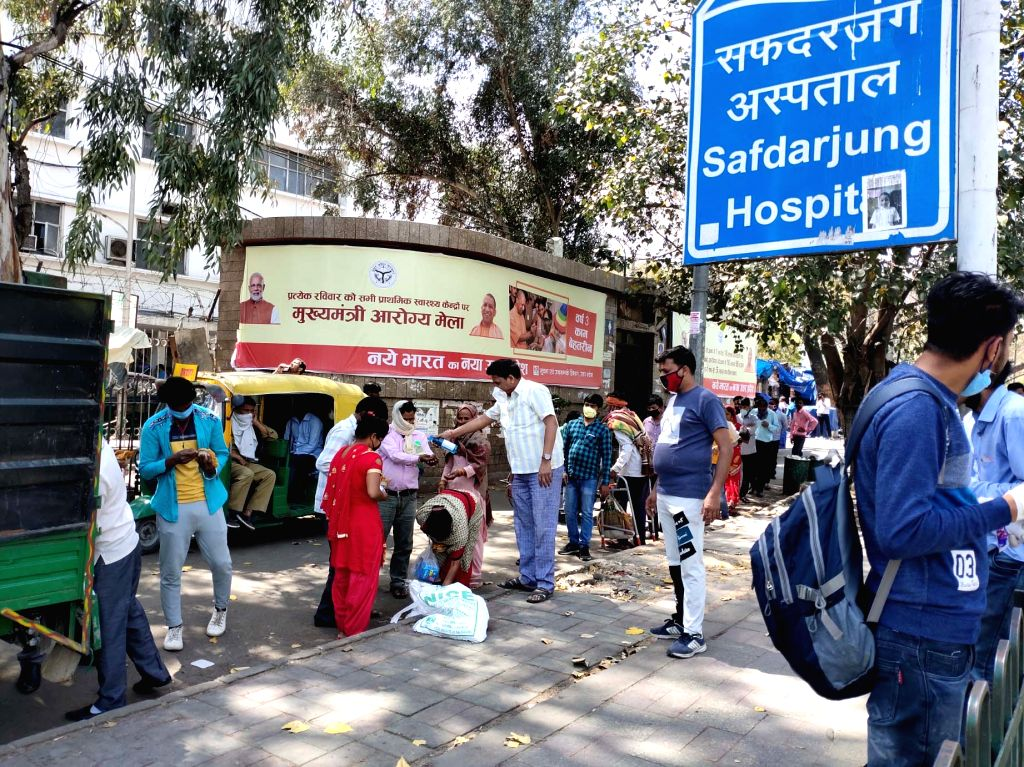 New Delhi: People being distributed food outside Delhi's Safdarjung Hospital on Day 6 of the 21-day nationwide lockdown imposed to contain the spread of coronavirus, on March 30, 2020. (Photo: IANS)