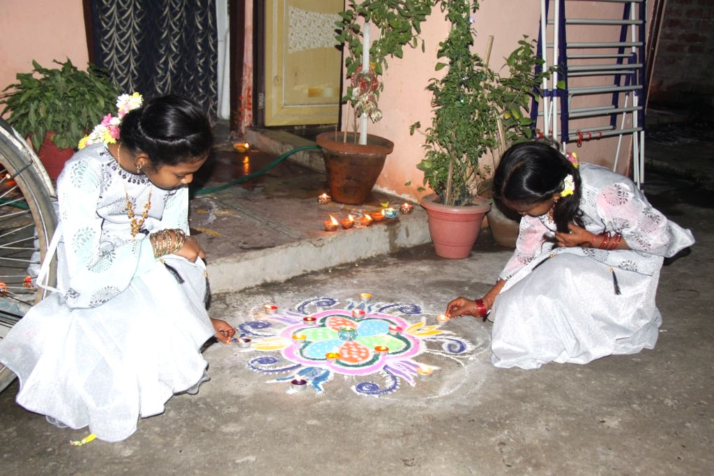 New Delhi: People celebrate Diwali by lighting up earthen lamps and making colorful rangolis outside their residence, in New Delhi on Nov 14, 202o. (Photo: IANS)