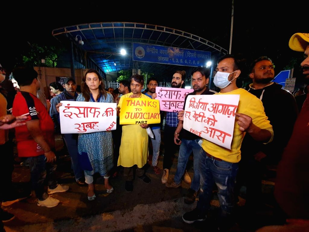 New Delhi: People hold posters outside the Tihar Jail ahead of the hanging of four convicts in the 2012 Nirbhaya rape case, in New Delhi on March 20, 2020. (Photo: IANS)