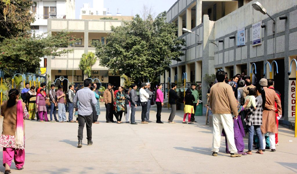 People queue-up to cast their votes at a polling booth during Delhi Assembly Polls in New Delhi, on Feb 7, 2015.