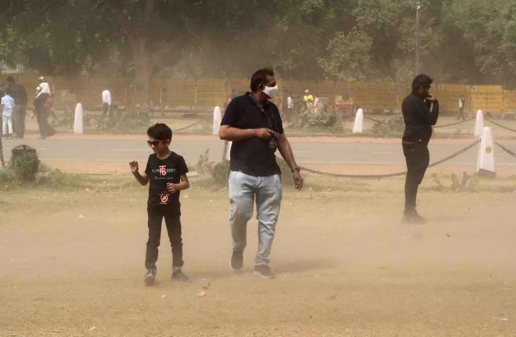 New Delhi: People stuck during the heavy dust storm at India Gate lawn in new Delhi on Monday March 30, 2021.(Photo:Wasim Sarvar/IANS)