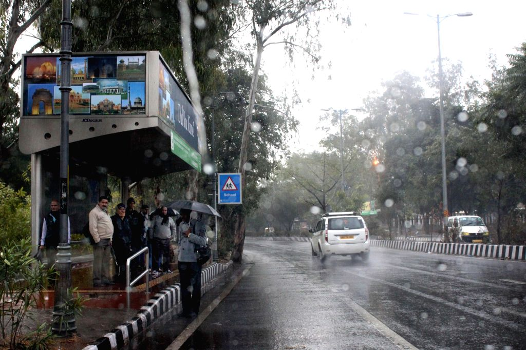 People take shelter under a bus stop to prevent themselves from winter rains, in New Delhi, on Jan 2, 2015.