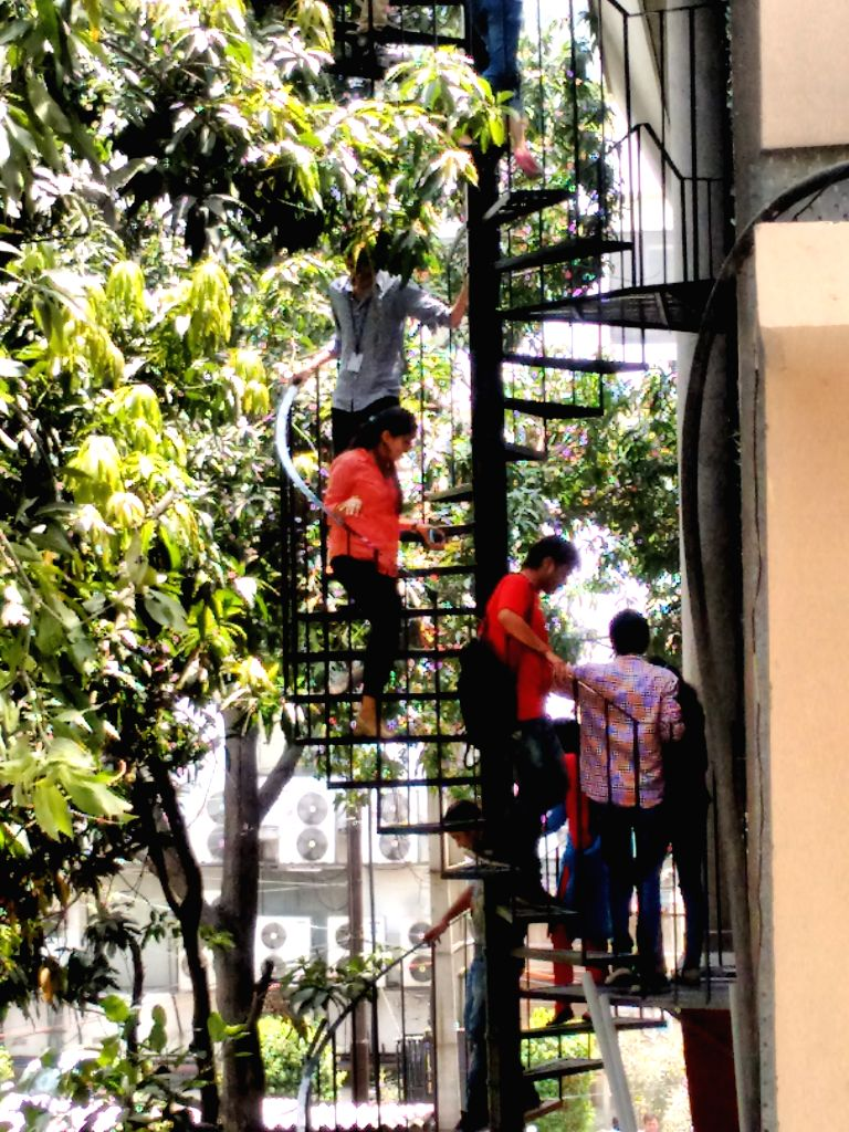 People use emergency exit to evacuate an office building in Noida on April 25, 2015. A strong earthquake measuring 7.5 on the Richter scale rocked Nepal, the tremors of which were felt ...