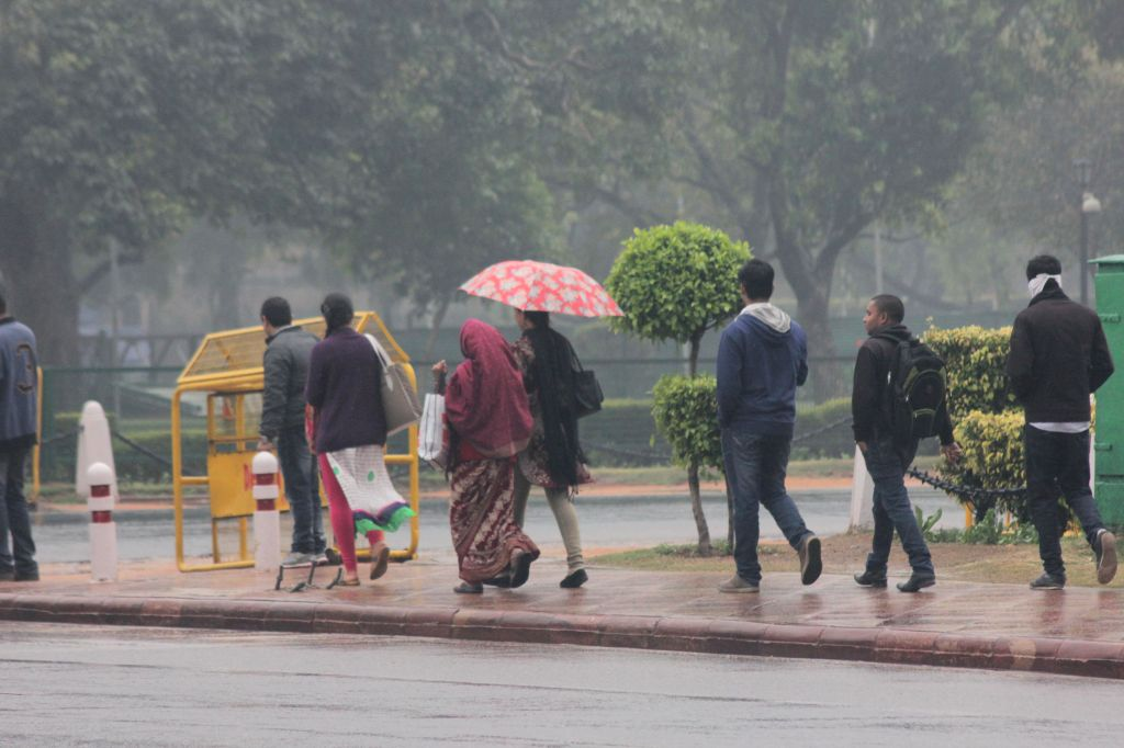 People use umbrellas to shield themselves from winter rains in New Delhi on Dec 14, 2014.