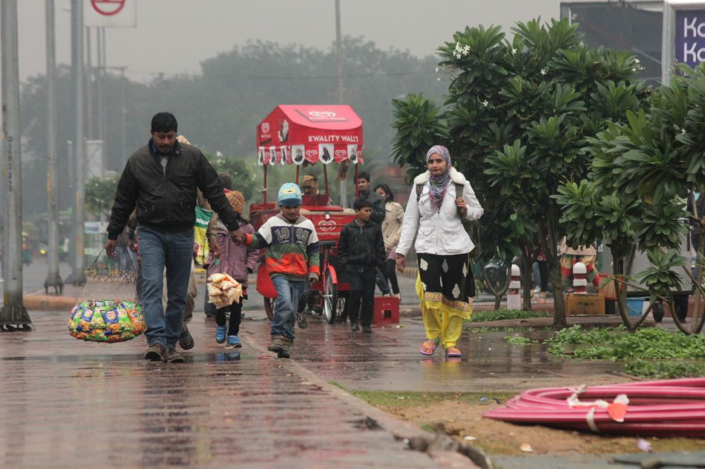 People visit India Gate during winter rains in New Delhi on Dec 14, 2014.