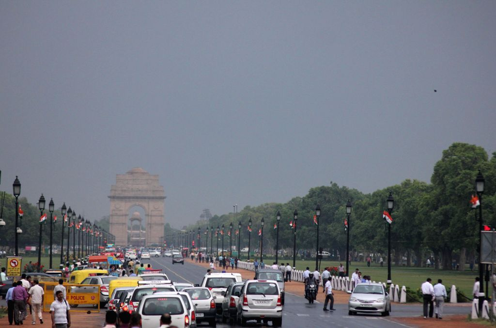 People walk at the Rajpath as it rains in New Delhi on May 13, 2015.