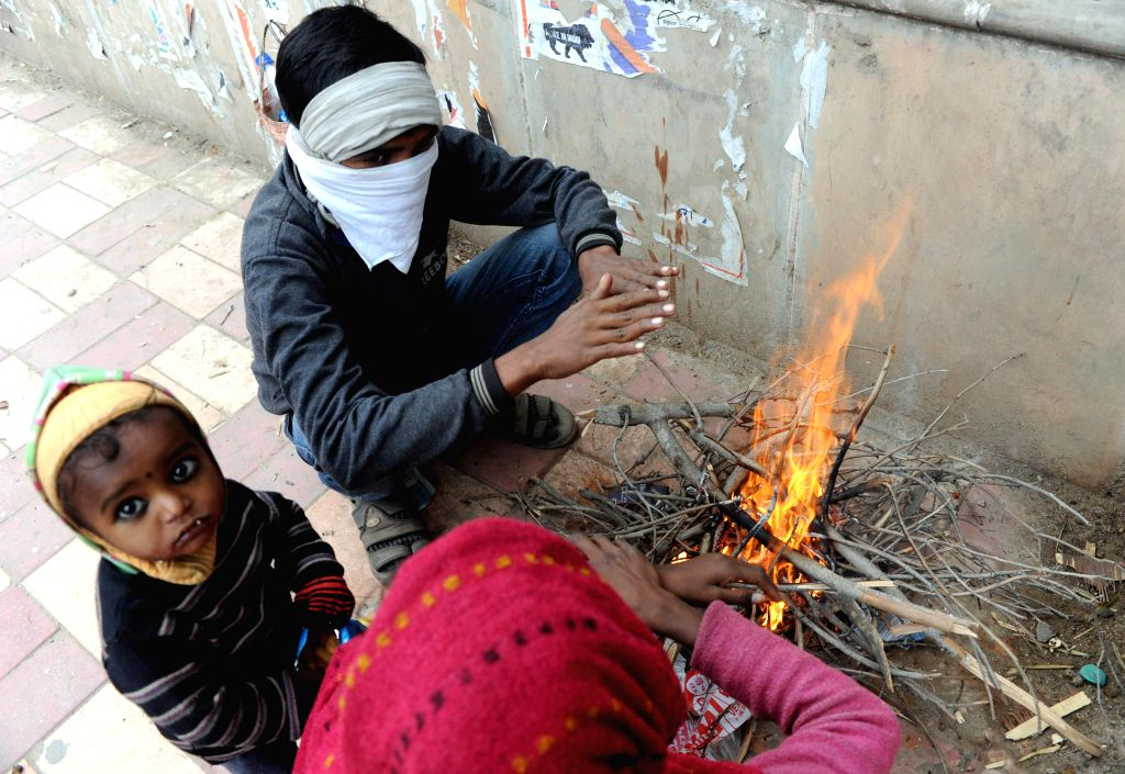 People warm themselves around a fire in New Delhi on Dec 22, 2014.