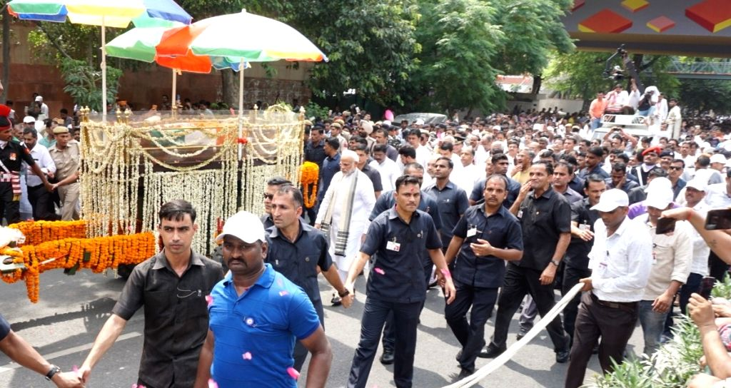 :New Delhi: Prime Minister Narendra Modi and BJP chief Amit Shah walk along with the convoy carrying the mortal remains of former Prime Minister Atal Bihari Vajpayee; in New Delhi on Aug 17, 2018. ...