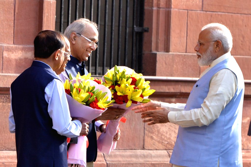 New Delhi: Prime Minister Narendra Modi being felicitated by the Principal Secretary to the Prime Minister, Nripendra Misra, National Security Adviser Ajit Doval and the Additional Principal Secretary to the Prime Minister P.K. Mishra at South Block  - Narendra Modi and K. Mishra