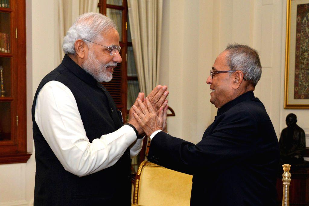 Prime Minister Narendra Modi calls on President Pranab Mukherjee to greet him on his 78th birthday at Rashtrapati Bhavan in New Delhi, on Dec 11, 2014. - Narendra Modi and Pranab Mukherjee