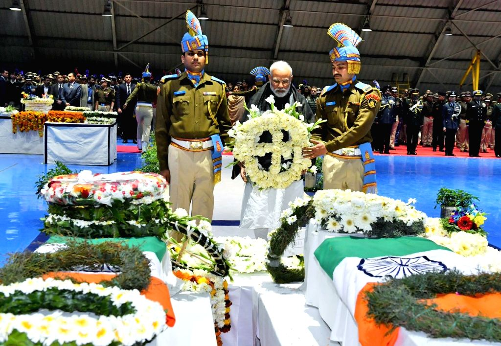 New Delhi: Prime Minister Narendra Modi lays wreath on the coffins of CRPF personnel who were killed in a suicide attack by militants in Jammu and Kashmir's Pulwama district on 14th Feb 2019; at Palam Airport in New Delhi on Feb 15, 2019. (Photo: IAN - Narendra Modi