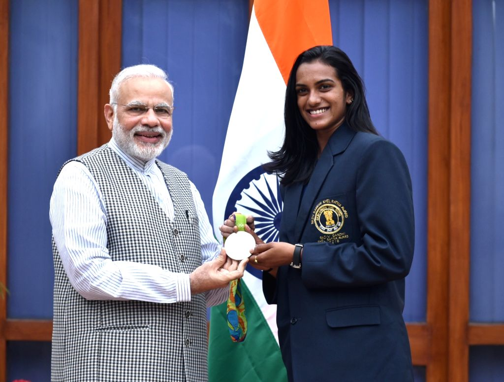 New Delhi: Prime Minister Narendra Modi with the Rio Olympic Silver Medal Winner & Rajiv Gandhi Khel Ratna Awardee of 2016, Indian shuttler P.V. Sindhu, in New Delhi on Aug 28, 2016. (Photo: IANS/PIB) - Narendra Modi