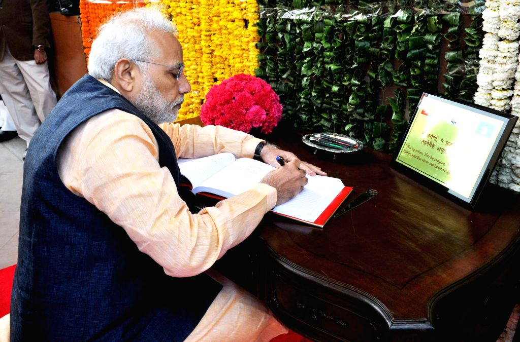 Prime Minister Narendra Modi writes on the visitor's book at the Amar Jawan Jyoti, on the occasion of the Centenary commemoration of World War - I, in New Delhi on March 10, 2015. - Narendra Modi