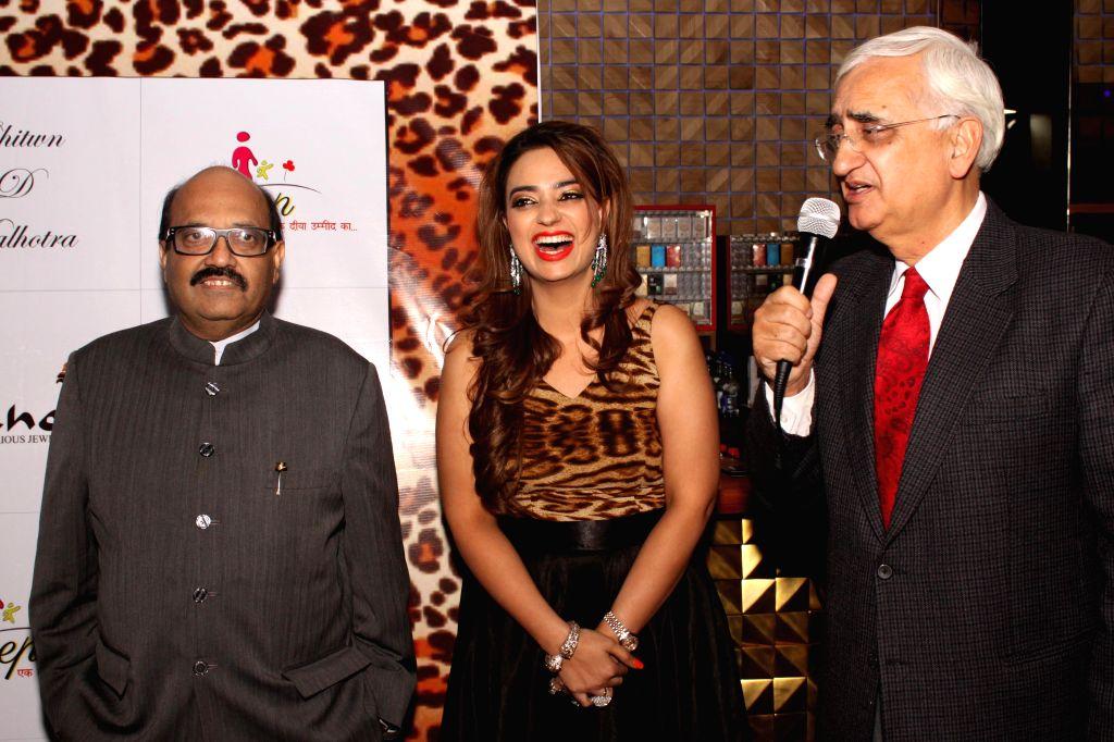 Rajya Sabha member Amar Singh (L) and Congress leader Salman Khurshid (R) during the launch of jewellery designer Chitwan Malhotra's (C) collection in New Delhi on Dec 9, 2014.