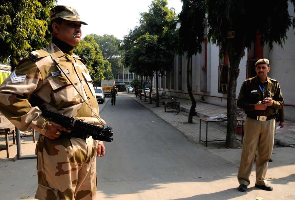 Security personnel in large numbers deployed outside a strong room whe EVMs are stored after Delhi Assembly Polls in in New Delhi, on Feb 8, 2015.
