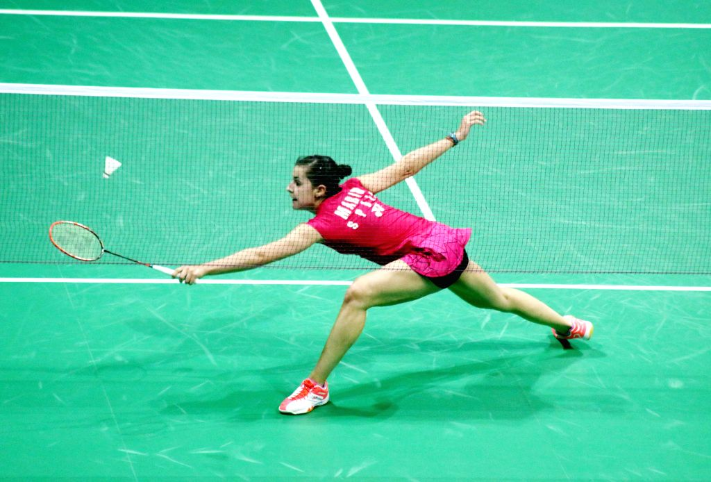 Spanish badminton player Carolina Marin returns a shot to Ratchanok Intanon of Thailand during a women`s singles match of Yonex Sunrise Indian Open Badminton Championship in New Delhi on ...