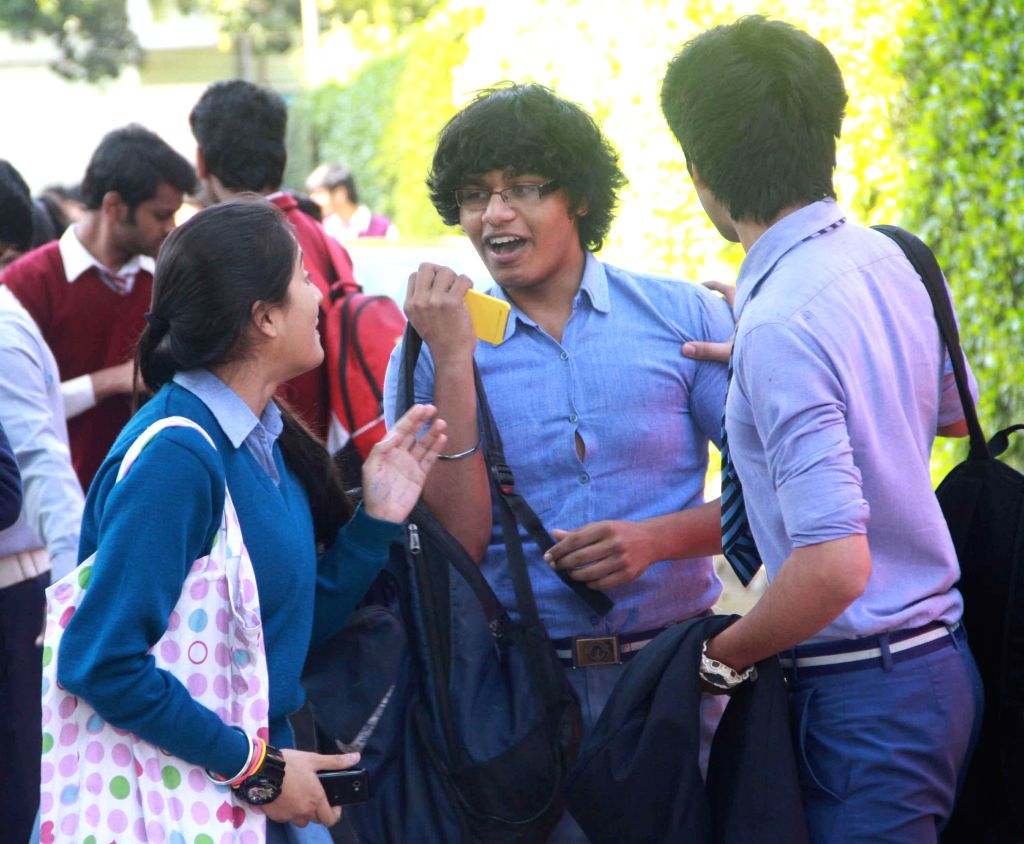 Students discuss question paper after coming out of examination hall at St. Thomas School, in New Delhi, on March 4, 2015.