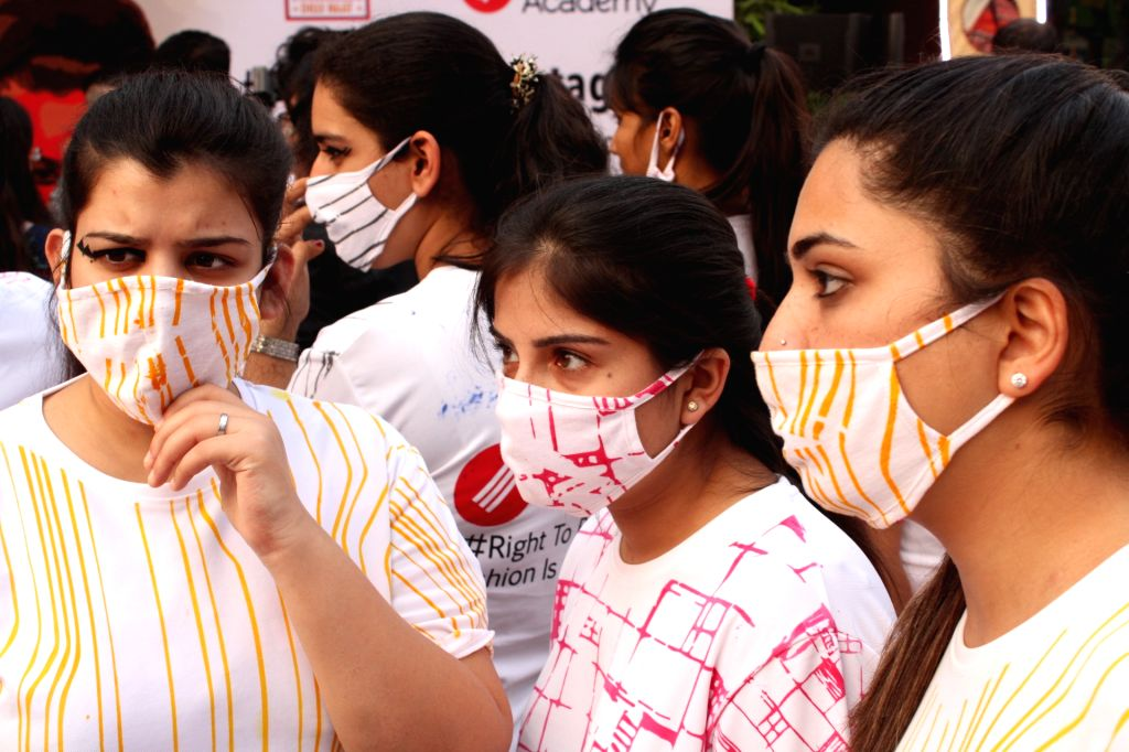 """New Delhi: Students participate in a """"Fashion March"""" to spread awareness regarding air pollution and usage of masks at Dilli Haat, INA in New Delhi, on Nov 2, 2018. (Photo: Amlan Paliwal/IANS)"""